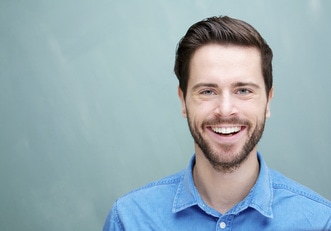 Caucasian man with short brown hair and facial hair smiling