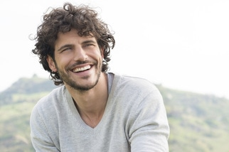 Caucasian man with curly brown hair smiling